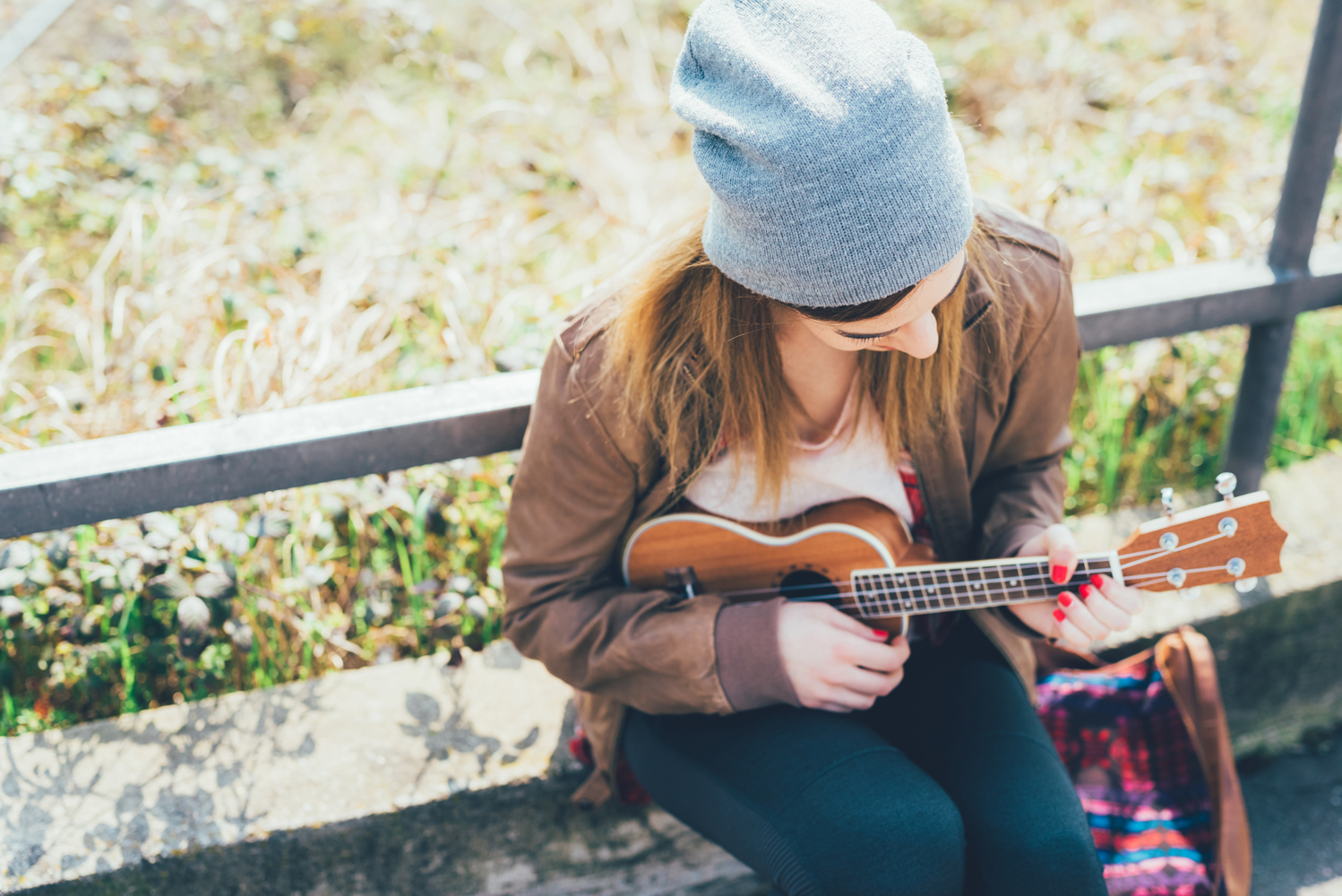 graphicstock young woman in the city playing ukulele busker musician composer concept HTRbpSF1
